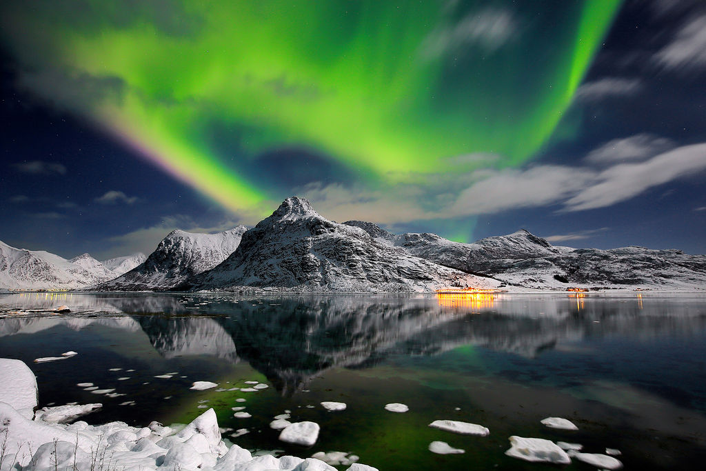 Aurora borealis in Lofoten islands, with snowy mountains reflected in the sea